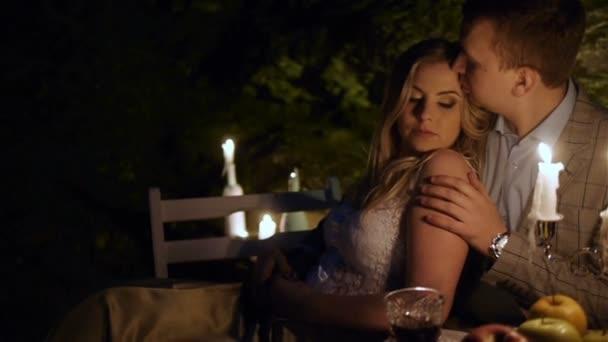 Pár na romantické rande, sedící u krásně prostřeného stolu večer venku. Večeře při svíčkách