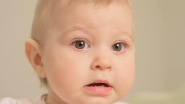 Holčička ve věku jednoho roku, psychicky a pečlivě prohlíží matka zblízka a smějící se, stojící na lůžku