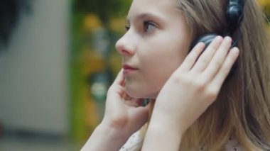 Attractive teenage girl with long hair listening to music on headphones