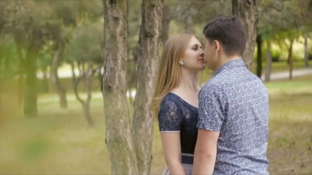A beautiful young couple in love stroll, kiss and hug in a summer park near coniferous trees