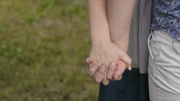 Milující chlap s ženou na procházce v parku v létě drží ruce zblízka