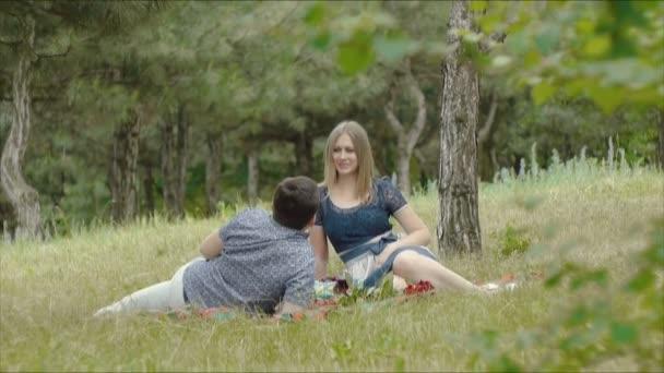 Mladý milující muž a žena v den sedět na trávě v parku letní a příjemné posezení