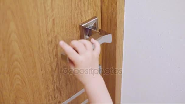 Malé dítě se pokusí otevřít dveře do místnosti tím, že dosáhne kliku