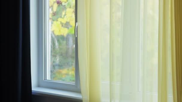 eine schlanke Frau mit langen blonden Haaren geht zum Fenster und schaut auf den Regen, der aus dem Fenster kommt