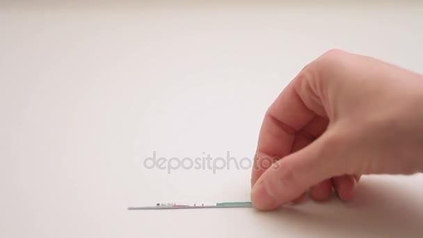 Closeup člověka hlazení Zenske ruky, další je těhotenský test s pozitivním výsledkem