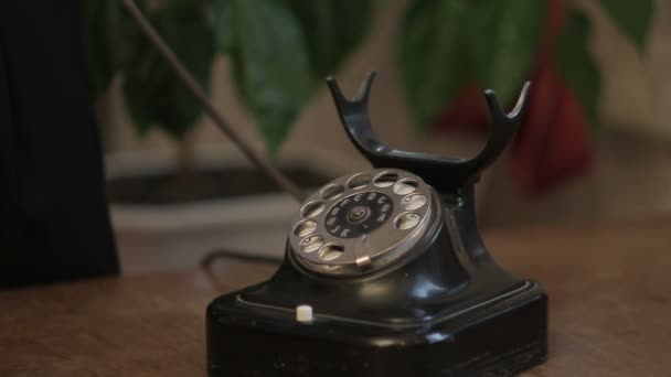 Closeup of an old black disk phone stands on an antique desk