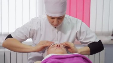 Procedures in a cosmetology clinic for a middle-aged woman. Close-up woman with mask being applied on her face