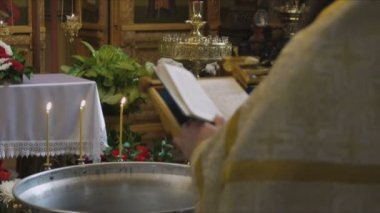 The Sacrament of Baptism in the Orthodox Church. Closeup of a priest reading the Gospel, standing in front of a font