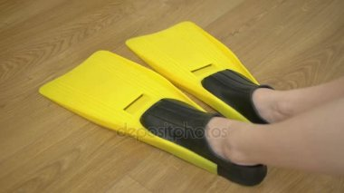 Legs of a woman, shod in fins for diving yellow color, lies on the floor in the room and moves her legs