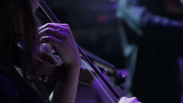 Eine Nahaufnahme von einer Musikerin tuning eine Geige vor der Ausführung in einer Sinfonie-Halle