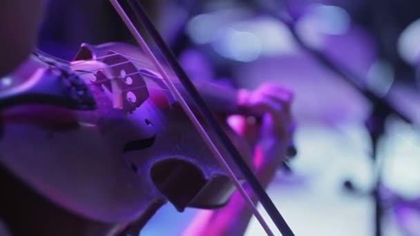 A vértes a hegedű hangolás végrehajtása a symphony hall előtt női zenész.