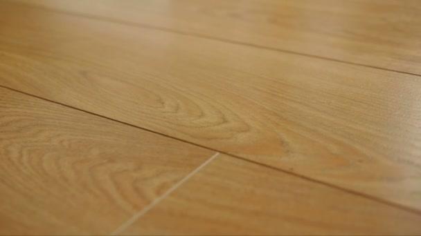 die Kamera bewegt sich auf dem Boden, der mit laminiertem Parkett mit brauner Holzstruktur bedeckt ist