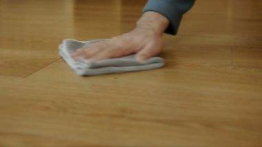 Huisvrouw polijsten houten vloer in flat met speciale product