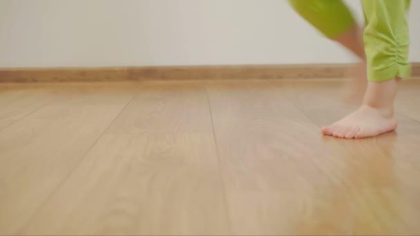 Detailní záběr na nohy malé dítě tančí a dupání na dřevěnou podlahu v místnosti