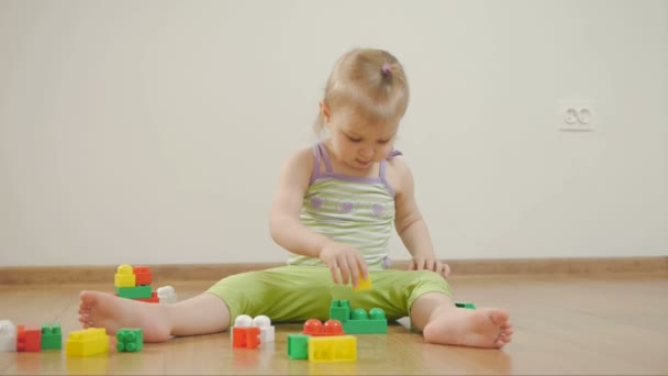 Little girl playing in colored blocks, sitting on white background. Child and toys.