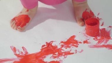 Closeup of a little girl with her hands dirty in red paint draws her fingers on a large sheet of white paper sitting on the floor