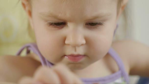 Malá holčička v barevných bloků, sedí na bílém pozadí. Děti a hračky.