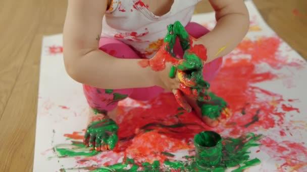 Holčička s rozmazaně malování prsty kreslí na velký list bílého papíru sedí na podlaze