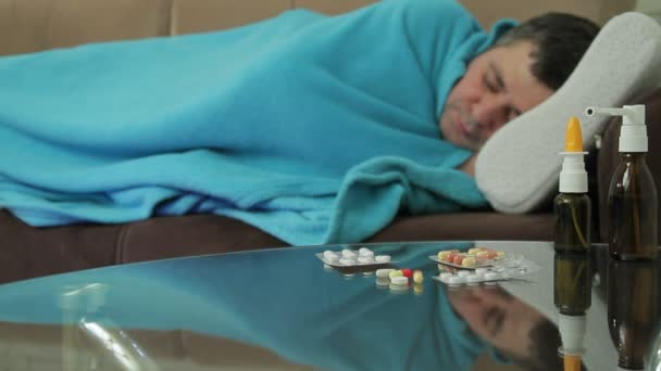 An adult man with symptoms of illness sleeps on the couch under cover of a blanket.