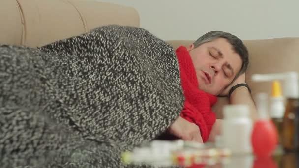 eine Person mit Erkältungsspuren liegt in der Wohnung auf der Couch und hustet stark