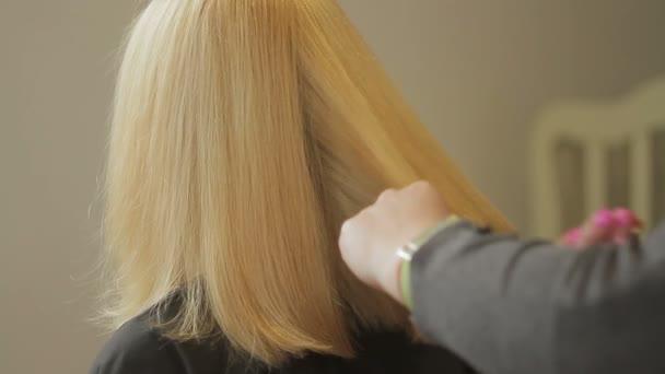 A fodrász Kombinált olló, egy nő, hosszú, szőke hajjal. Vértes fodrász