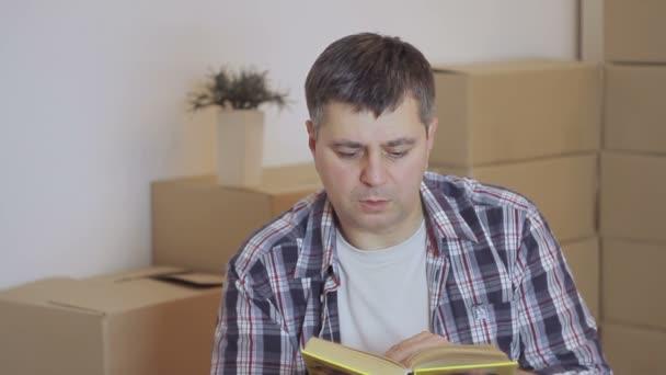 Muž v kostkované košili sedí na podlaze, čtení knihy v prázdném pokoji mezi kartonové krabice
