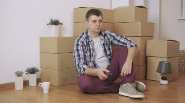 A man sits on the floor and switches TV channels, in a room with cardboard boxes
