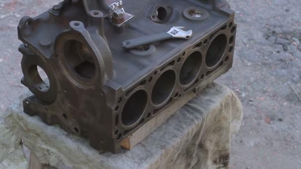 Közeli kép: a szétszerelt autó motor és a csavarkulcs