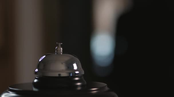 Closeup of a call to the front Desk of the hotel. Men finger presses the bell.