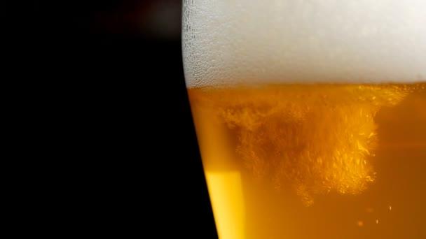 Detailní záběr jasně žlutého piva ve sklenici na tmavém pozadí