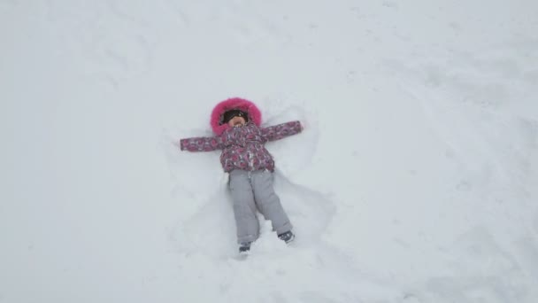 Happy Little Girl Laying Down on the Snow Making Snow Angel