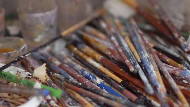 Mnoho štětců potřísněných barvou je na stole v ateliéru umělce.
