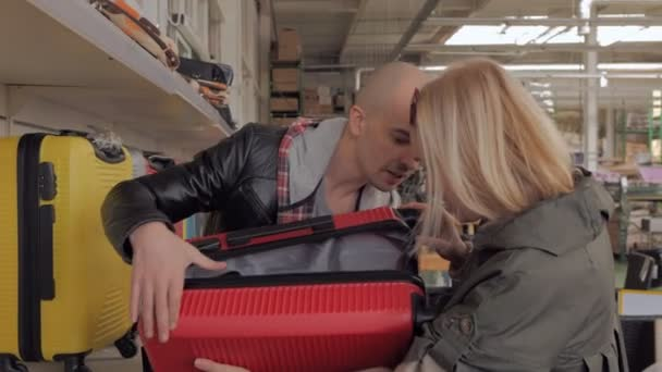 A couple in a shopping center choose a suitcase for travel.