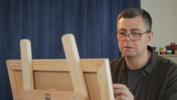 An artist working on a painting uses a brush to create a picture on an easel.