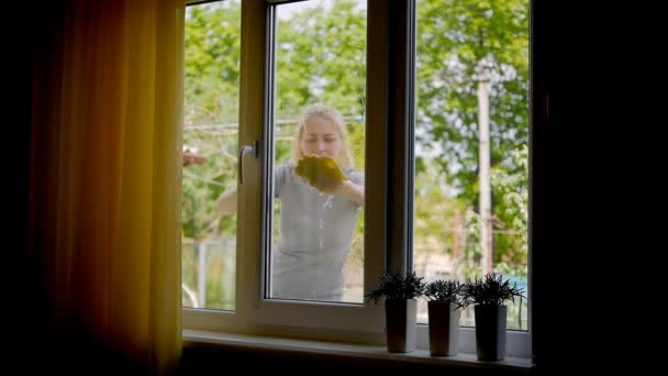 Žena před domem myje okno žlutou látkou a vodou..