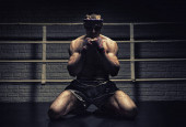 Photo Thai boxer prays in the ring. Mongkhon. The concept of tournamen
