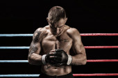 Photo Mixed martial artist posing in boxing ring. Concept of mma, ufc, thai boxing, classic boxing. Mixed media