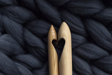 wooden knitting needles on background of grey merino wool blanke