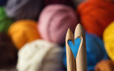 wooden knitting needles on background of colorful merino wool ba