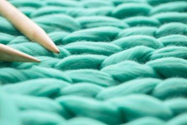 wooden knitting needles on background of merino wool blanket