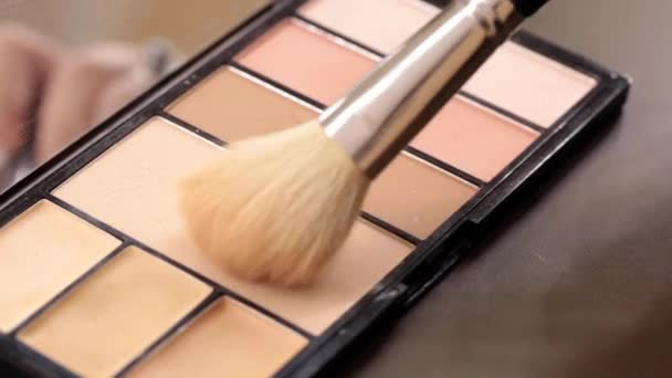 Close up of makeup brush moving over eye shadows