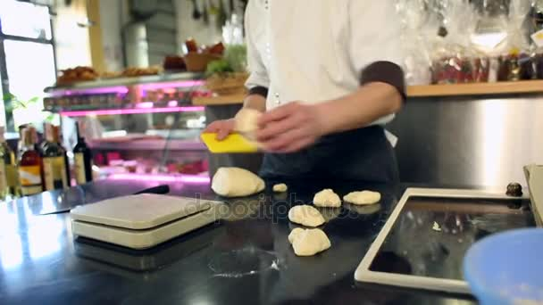 Baker hands cutting dough in flour on table