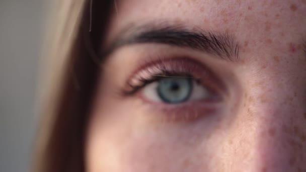 Egy kék szemű részlete rémült lány szeplő egy mozgó kamera egy elmosódott háttér.