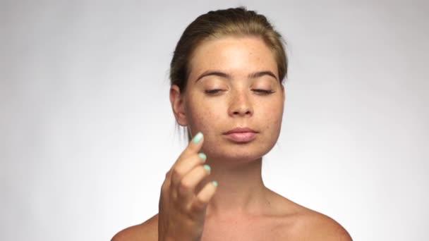 Krásná žena s pihy, použije krém dojemné a kontrolu její kůži, Glamour girl s make-up, světlé pozadí