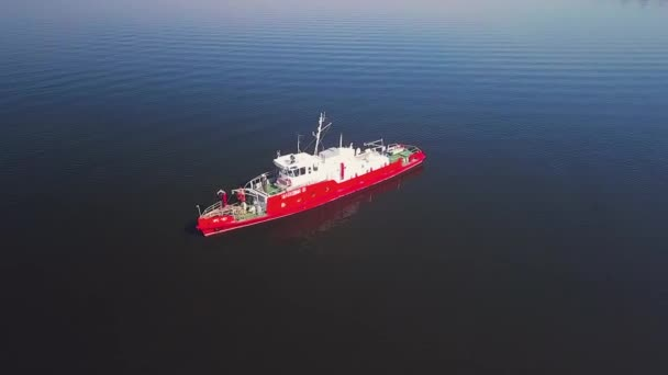 Blick von einer Drohne auf ein rotes Rettungsschiff. Matrosen arbeiten daran.