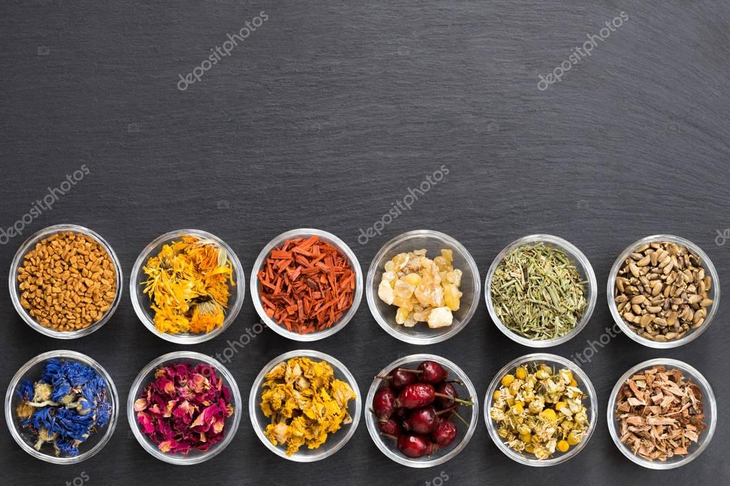 Selection of dried herbs on a dark background with copy space, top view