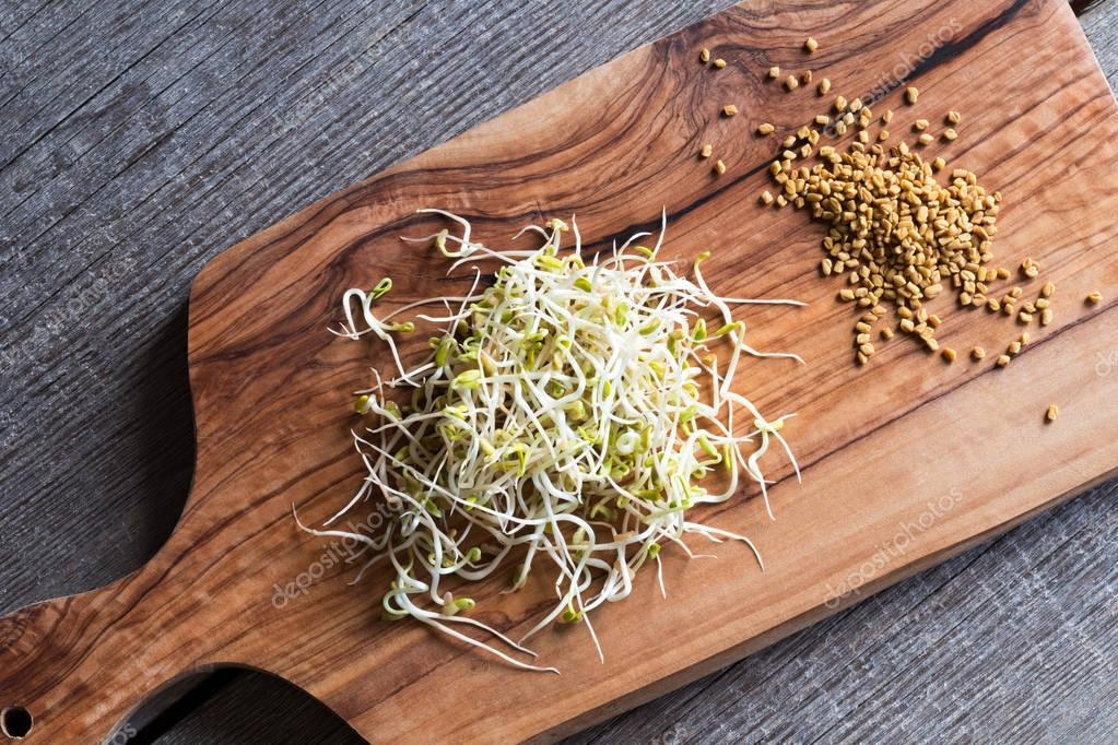 Dry and sprouted fenugreek seeds on a wooden cutting board