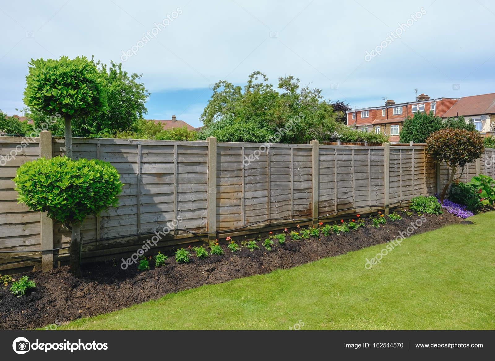 Plate-bande soignée avec barrière de jardin et pelouse ...