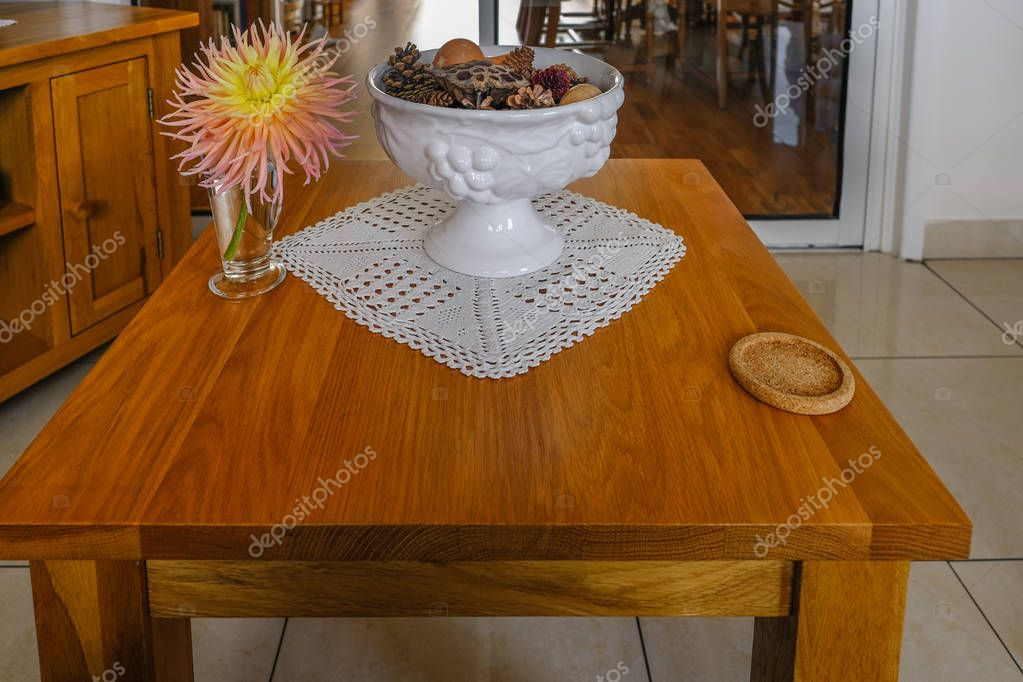 Oak coffee table with coaster, bowl and dalhia flower in vase.