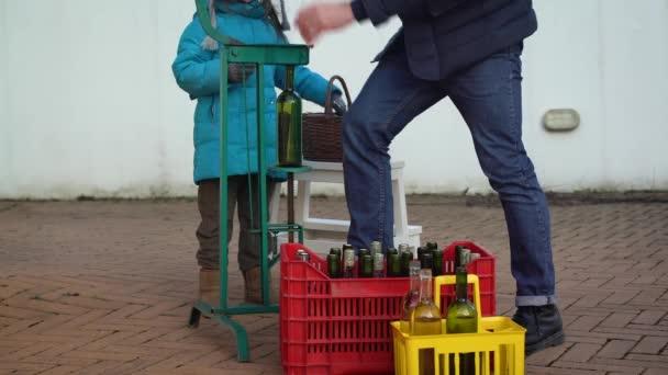 Malá holčička pomáhá svému otci uzavřít bílé vinné lahve s on má doplňovat dříve, Selektivní ostření